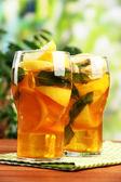 Chá gelado com limão e hortelã na mesa de madeira, ao ar livre — Foto Stock