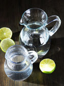 Glass pitchers of water on wooden table close-up — Stock Photo