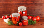 Tasty canned and fresh tomatoes on wooden table — Stock Photo