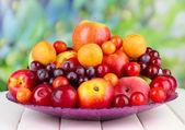 Variedade de frutas suculentas na mesa de madeira, no fundo brilhante — Foto Stock