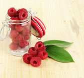 Ripe raspberries in bank on wooden table close-up — Stock Photo