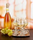 Weisswein glas und flasche auf zimmer-hintergrund — Stockfoto