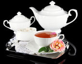 Chaleira e xícara de chá de chá rosa na bandeja metálica sobre fundo preto guardanapo — Foto Stock