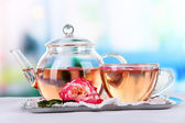 Kettle cup of tea from tea rose on metallic tray on tablecloth — Stock Photo