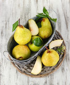 Pears in basket on braided tray on wooden table — Stock Photo