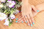 Beautiful woman hands with blue manicure near bouquet of beautiful flowers, on color background — Stock Photo