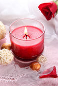 Beautiful red candle with flower petals in water — Stock Photo