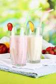 Delicious milk shakes with strawberries and peach on wooden table on natural background — Stock Photo