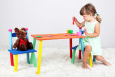 Little cute girl sitting on little chair near table, on gray background — Stock Photo