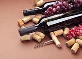 Garrafas de vinho, uvas e rolhas em fundo marrom — Foto Stock