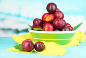 Ripe plums in bowl on wooden table on natural background — Stock Photo