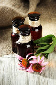 Medicine bottles with purple echinacea flowers on wooden table with burlap — Fotografia Stock