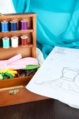 Sewing kit in wooden box,cloth and sketch on wooden table — Stock Photo