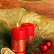 Two candles and Christmas decorations, on wooden background — Stock Photo #29091719