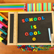 Stockfoto: Small chalkboard with school supplies on wooden background. Back to School