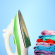 Steam iron with clothes, on color background — Stock Photo