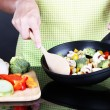 Hands cooking vegetable ragout in pan on gray background — Stock Photo #29093565