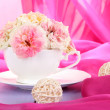 Roses in cup on wooden table on pink cloth background — Stock Photo