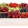 Different summer berries in wooden crate isolated on white — Stock Photo #29094137