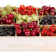Different summer berries in wooden crate isolated on white — Stock Photo