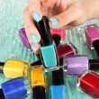 Stock Photo: Beautiful woman hands with blue manicure and several bottles with nail polish, on color background