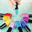 Beautiful woman hands with blue manicure and several bottles with nail polish, on color background — Stock Photo #29094289