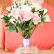 Woman holding bouquet of roses, on bright background, close-up — Stock Photo