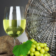 Ripe delicious grapes with glass of wine on table on gray background — Stock Photo #29094519