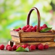 Ripe sweet raspberries in basket on wooden table, on green background — Stock Photo