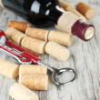 Corkscrew with wine corks and bottle of wine on wooden table close-up — Stock Photo #29095539