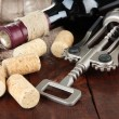 Corkscrew with wine corks and bottle of wine on wooden table close-up — Stock Photo #29095545