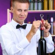 Bartender opens bottle of wine — Stock Photo #29097017