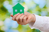 Concept: woman hand with paper house on green background, close up — Stock Photo