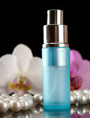 Women's perfume in beautiful bottle and orchid flowers, on black background — Stock Photo