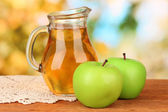 Full jug of apple juice and apple on wooden table on bright background — Stock Photo