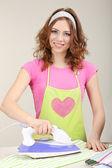 Young beautiful woman ironing clothes in room on grey background — Stock Photo