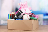 Children property in carton on table in room — Stock Photo