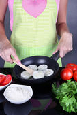Hands cooking marrows in pan on gray background — Stock Photo