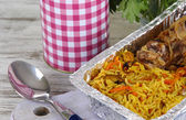 Food in boxes of foil on napkin on wooden board on wooden table — Stock Photo
