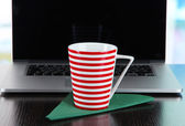 Striped cup on napkin on laptop background on wooden table — Stock Photo