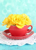 Roses in red cup on napkin on blue background — Stok fotoğraf