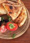 Pizza calzones on wooden board on wooden table — Stock Photo