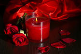 Красивый романтический красная свеча с цветами и шелковые ткани, крупным планом — Стоковое фото