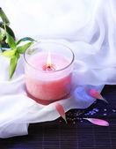 Beautiful pink candle on bamboo mat — Stock Photo