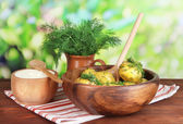 Boiled potatoes on wooden bowl on napkin on wooden table on nature background — Stock Photo