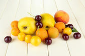 Bright summer fruits on wooden table close-up — Stock Photo