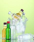 Bottiglie di minibar nel secchio con cubetti di ghiaccio, sul colore di sfondo — Foto Stock