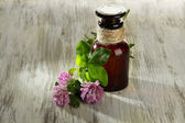 Medicine bottle with clover flowers on wooden table — Stock Photo