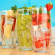 Glasses of fruit drinks with ice cubes on blue background — Stock Photo #29129803