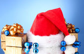 Beautiful Christmas hat, gifts and Christmas balls on blue background — 图库照片
